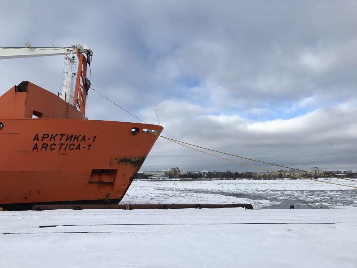 Punainen jäänmurtajan keula satamassa jäisessä meressä.