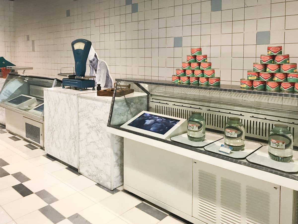 90-luvun alun elintarvikepulaa kuvataan näyttelyssä kaupantiskillä, jossa tarjolla on vain koivunmahlajuomaa ja merileväsäilykkeitä.