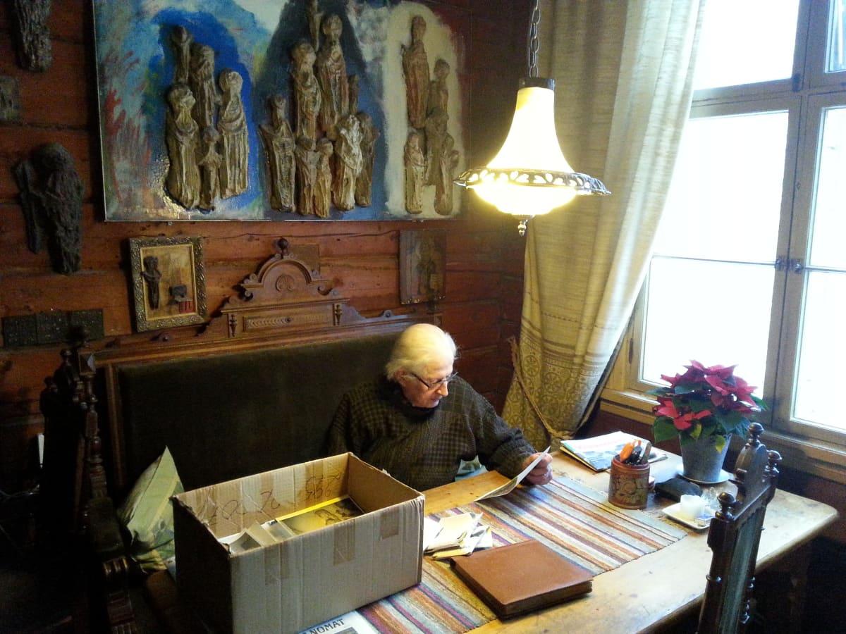 Ossi Somma selailee kotonaan valokuva-arkistojaan.
