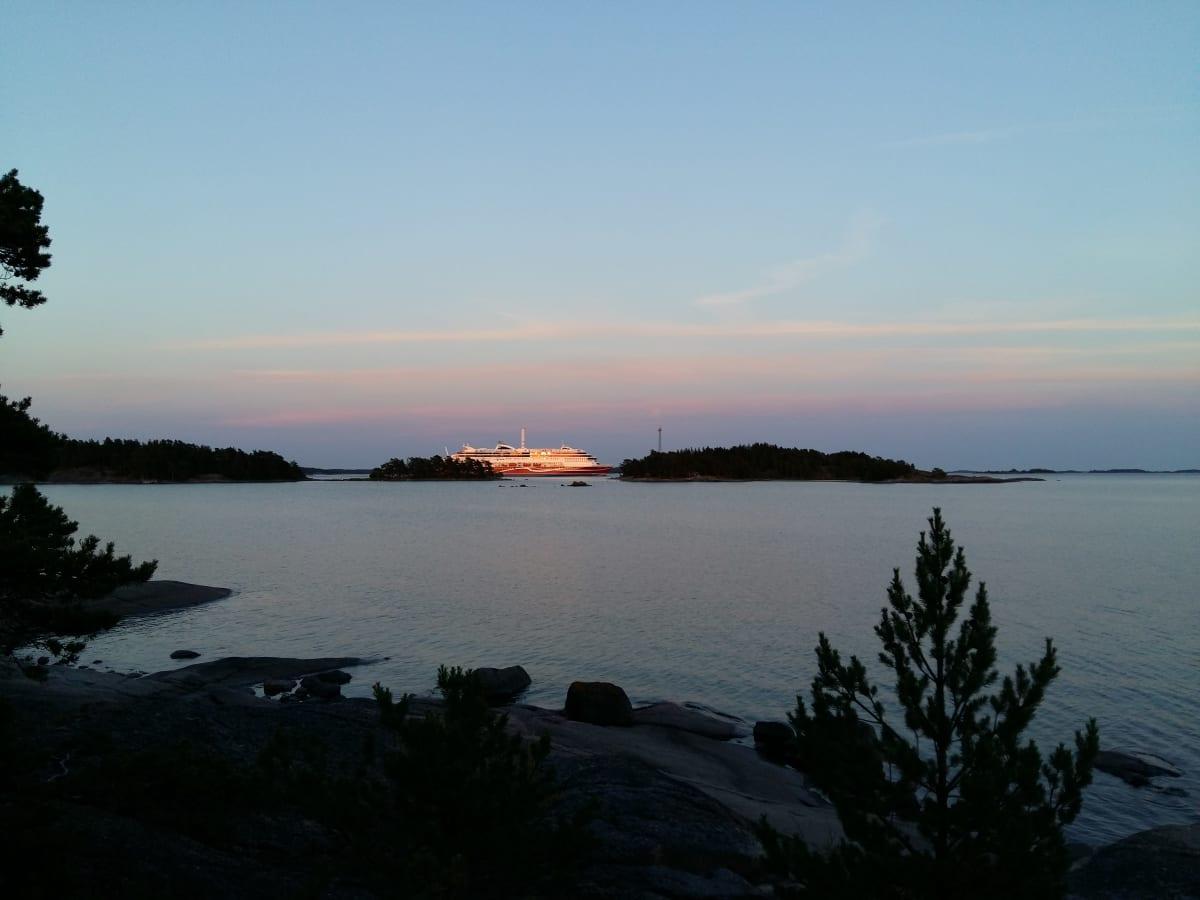 Ilta-auringon säteet värjäävät risteilyaluksen kylkiä saarten keskellä Houtskarissa Saaristomerellä.