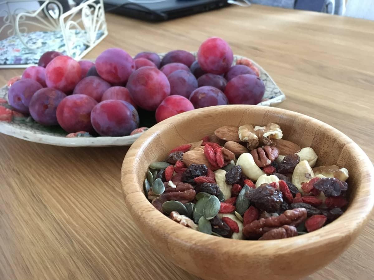 Kulho jossa pähkinöitä, siemeniä ja rusinoita sekä luumuja kulhollinen.