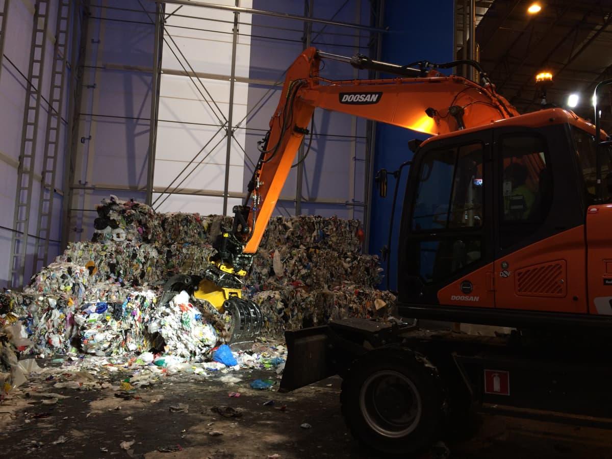 Kaivinkone työstää muovijätepaaleja