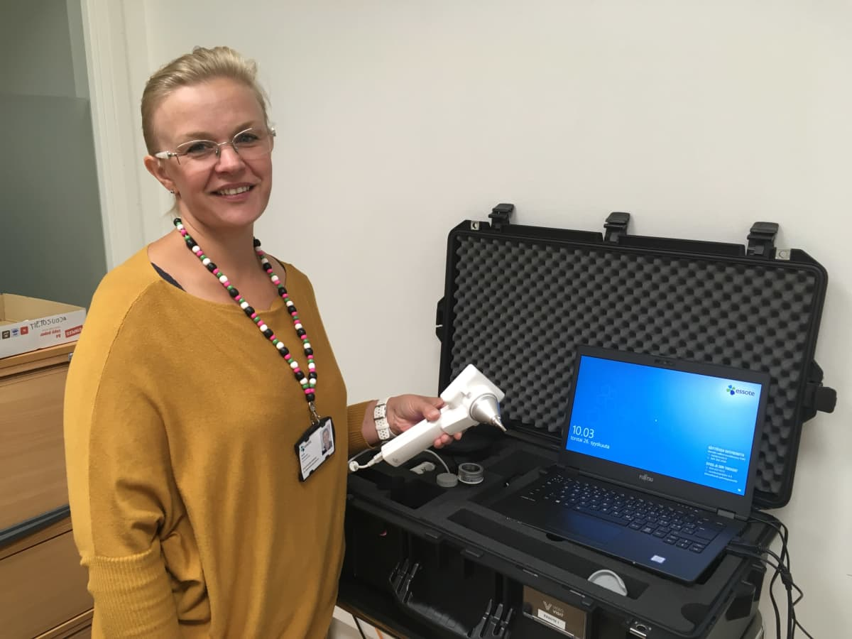 Sairaanhoitajalla on kädessään tutkimuskamera, jolla voi tutkia esimerkiksi korvat.