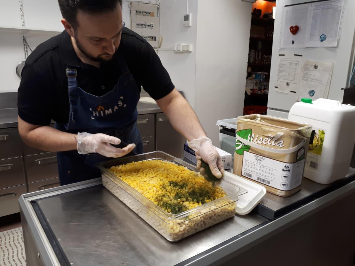 mies laittaa ruokaa ravintolassa