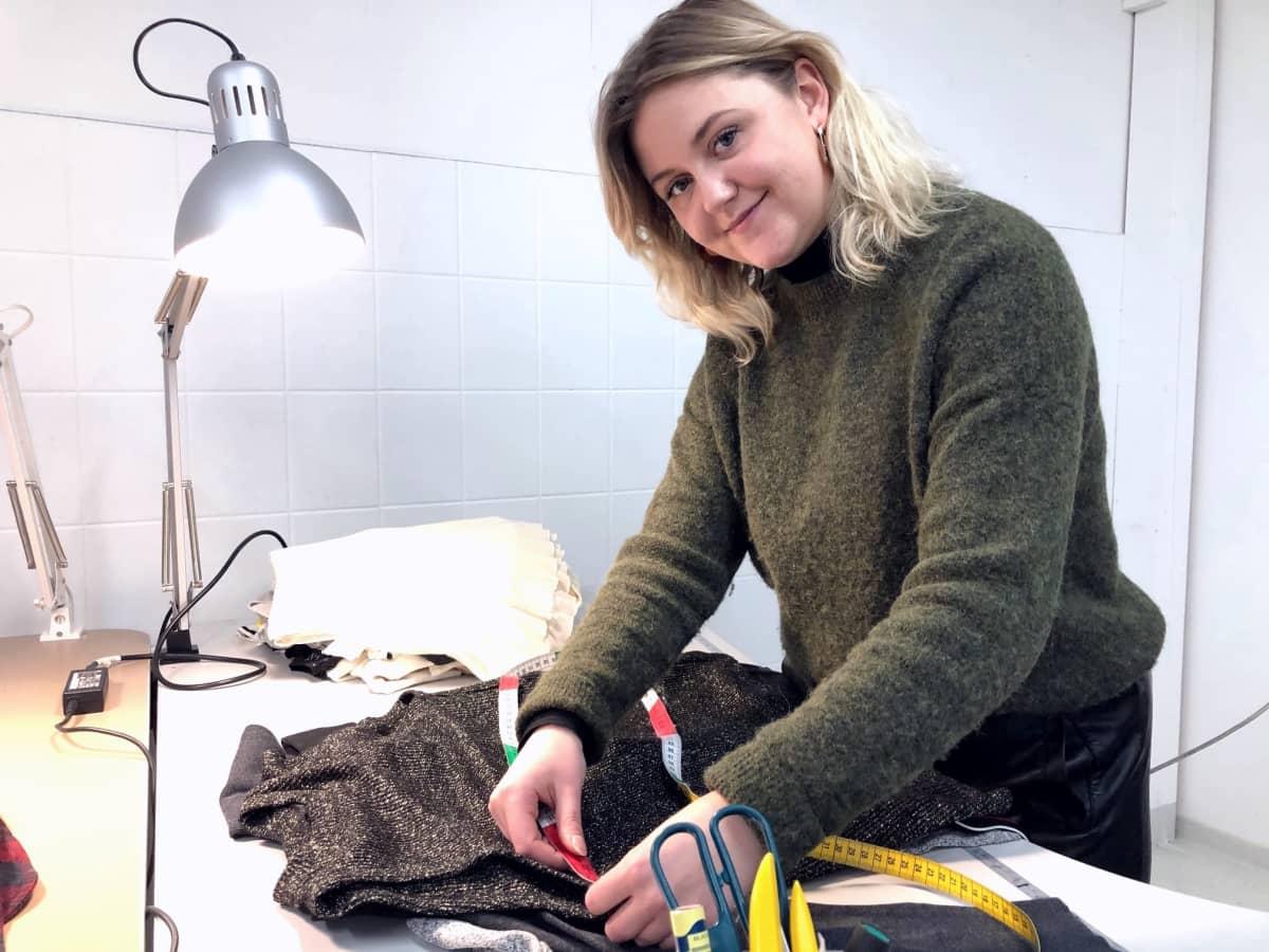 Nainen mittaa vaatteen koon mittanauhalla.