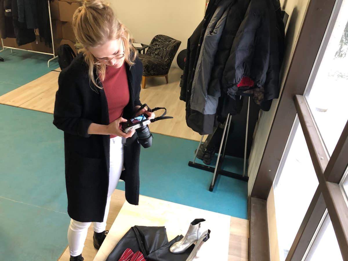 Nainen valokuvaa vaatteita vanerialustalla.