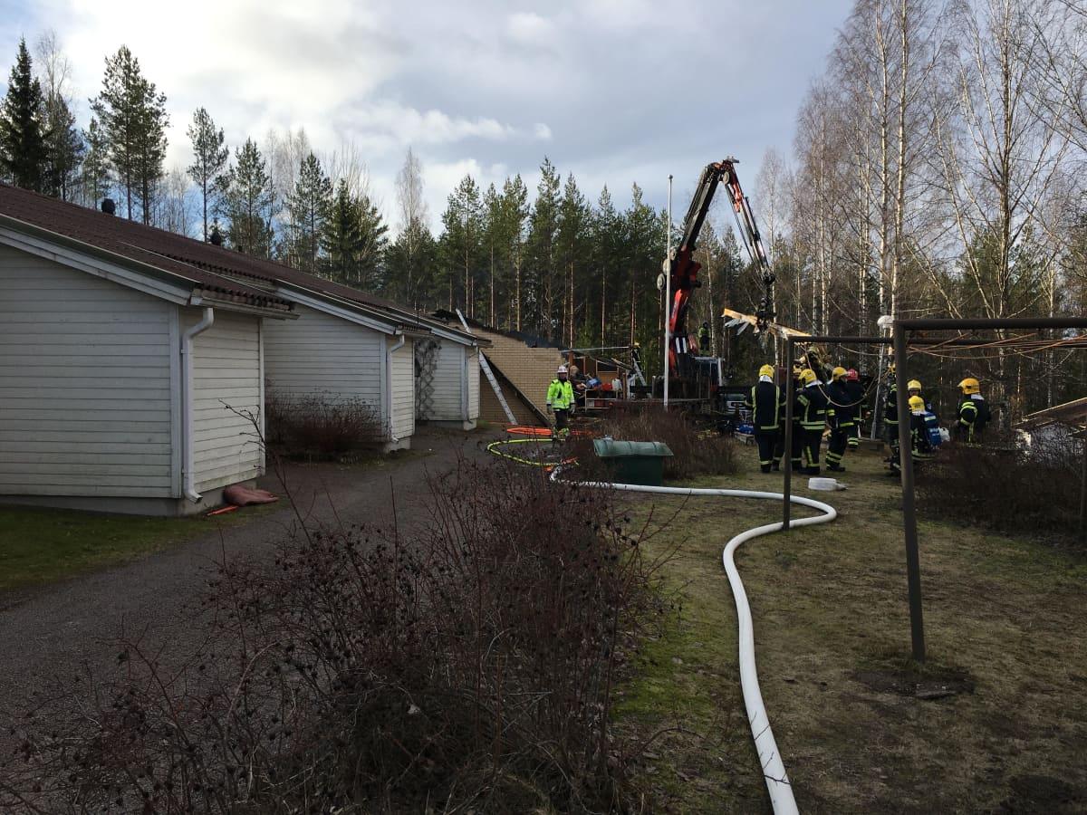 Palokunta tulipalopaikalla, rivitalon katto on palanut.