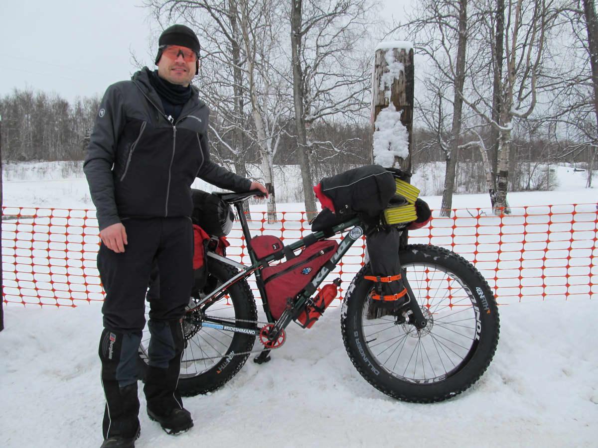 Toni Lund seisoo pyöränsä vieressä.