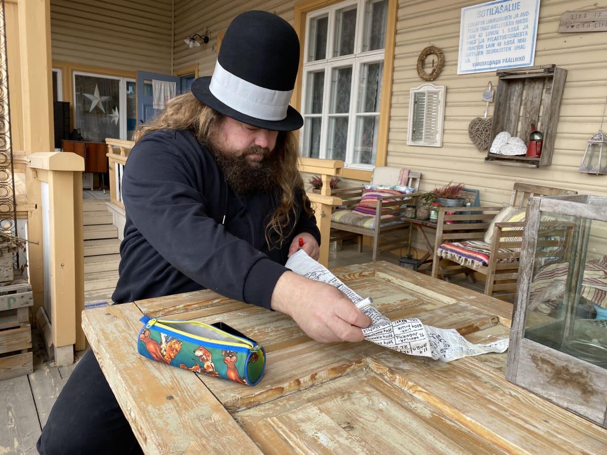Petteri Tikkanen suoristaa vessapaperirullalle piirrettyä sarjakuvaa pöydän ääressä terassilla.