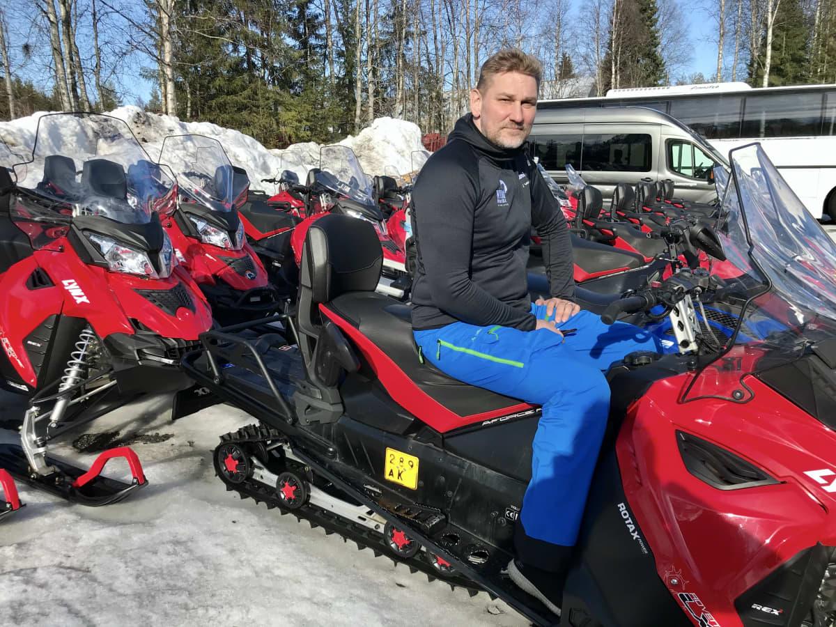 Rovaniemeläinen matkailuyrittäjä Sami Päivike safariyrityksensä moottorikelkkojen keskellä
