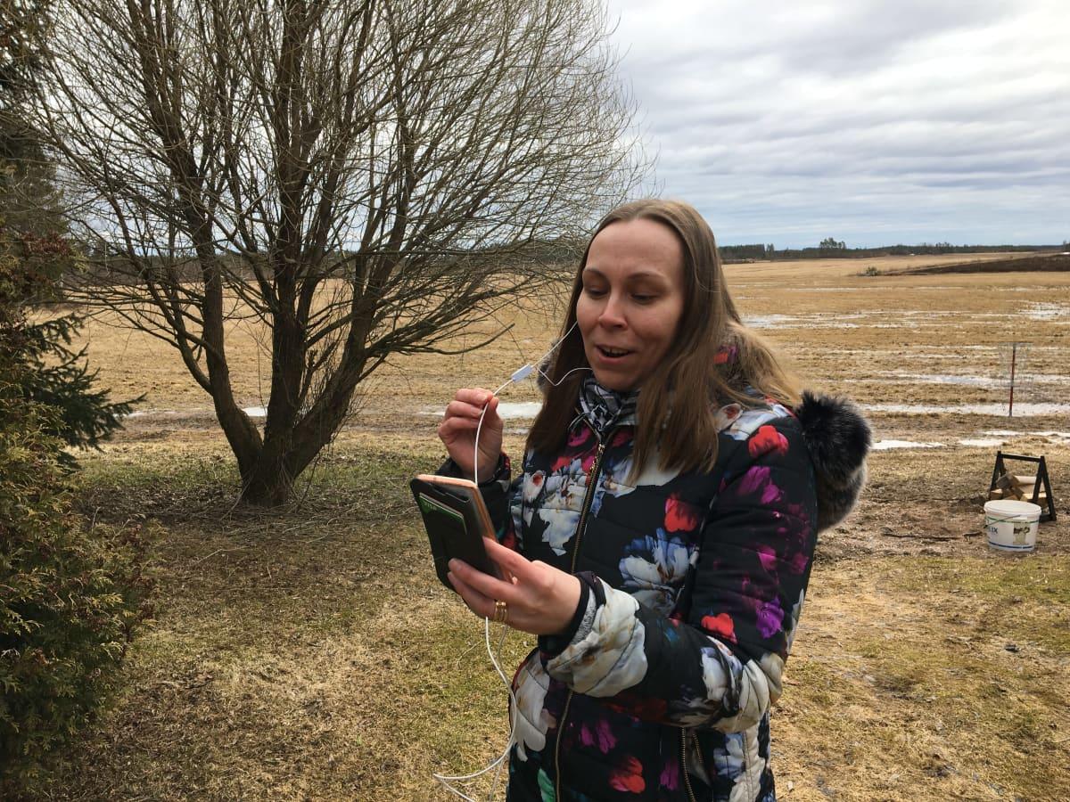 Kuvassa Johanna Paavola laulaa peltojen edessä.