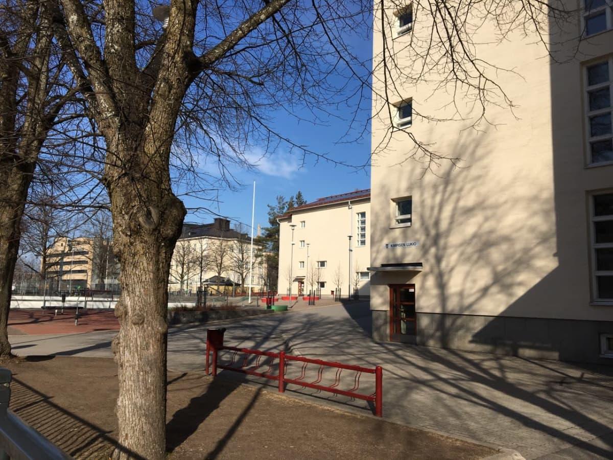 Tyhjä koulun piha, ympärillä korkeat koulurakennukset.