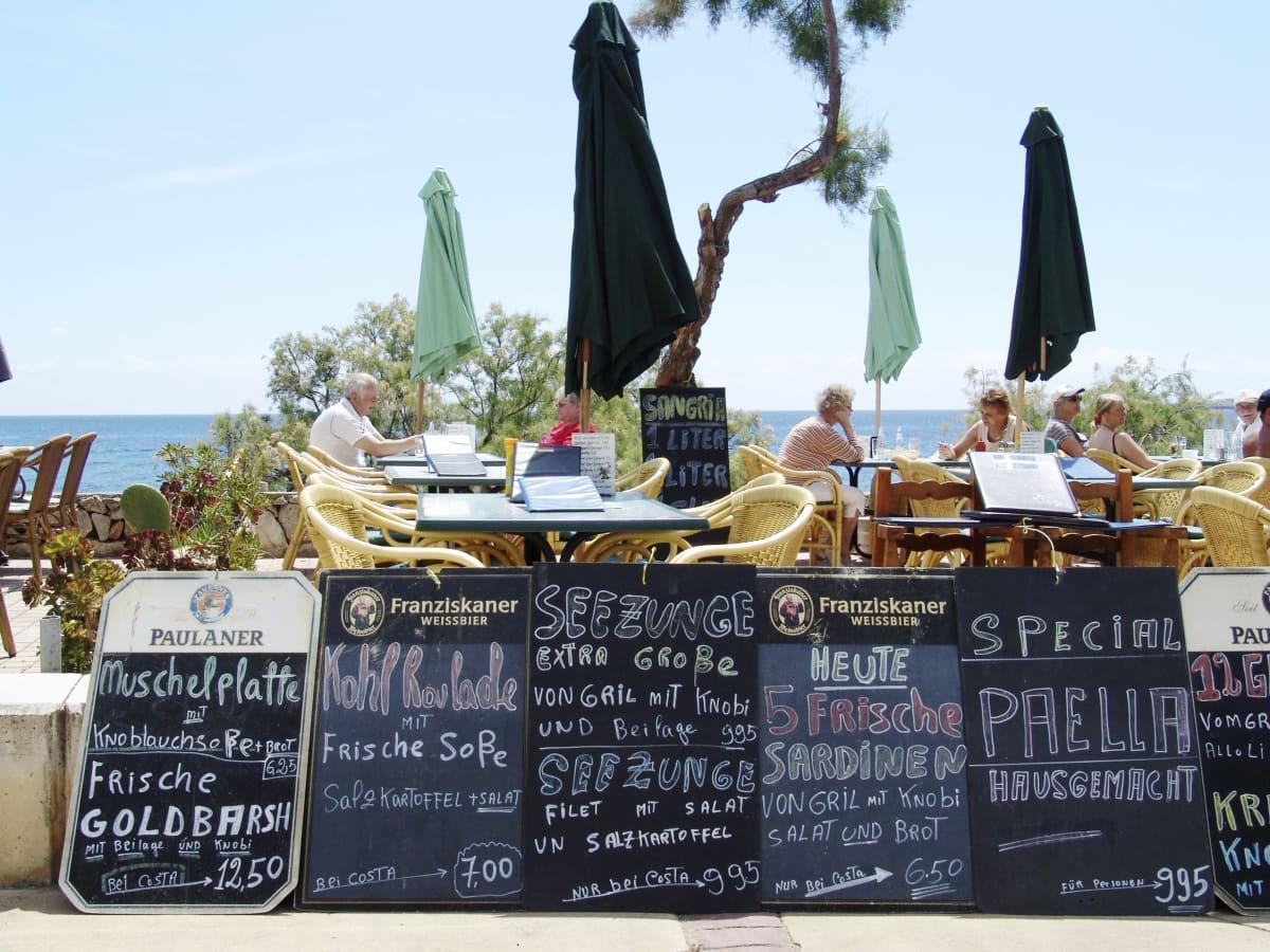 Ravintolan saksankielisiä tarjouskylttejä rantaterassin edessä