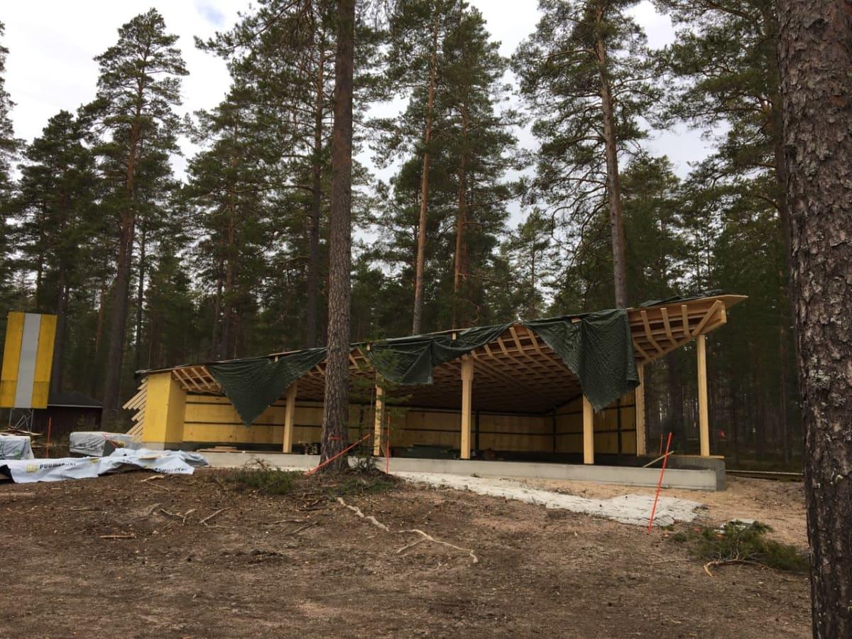 Metsässä rakenteilla oleva suuri katos, joka on etusivultaan auki.