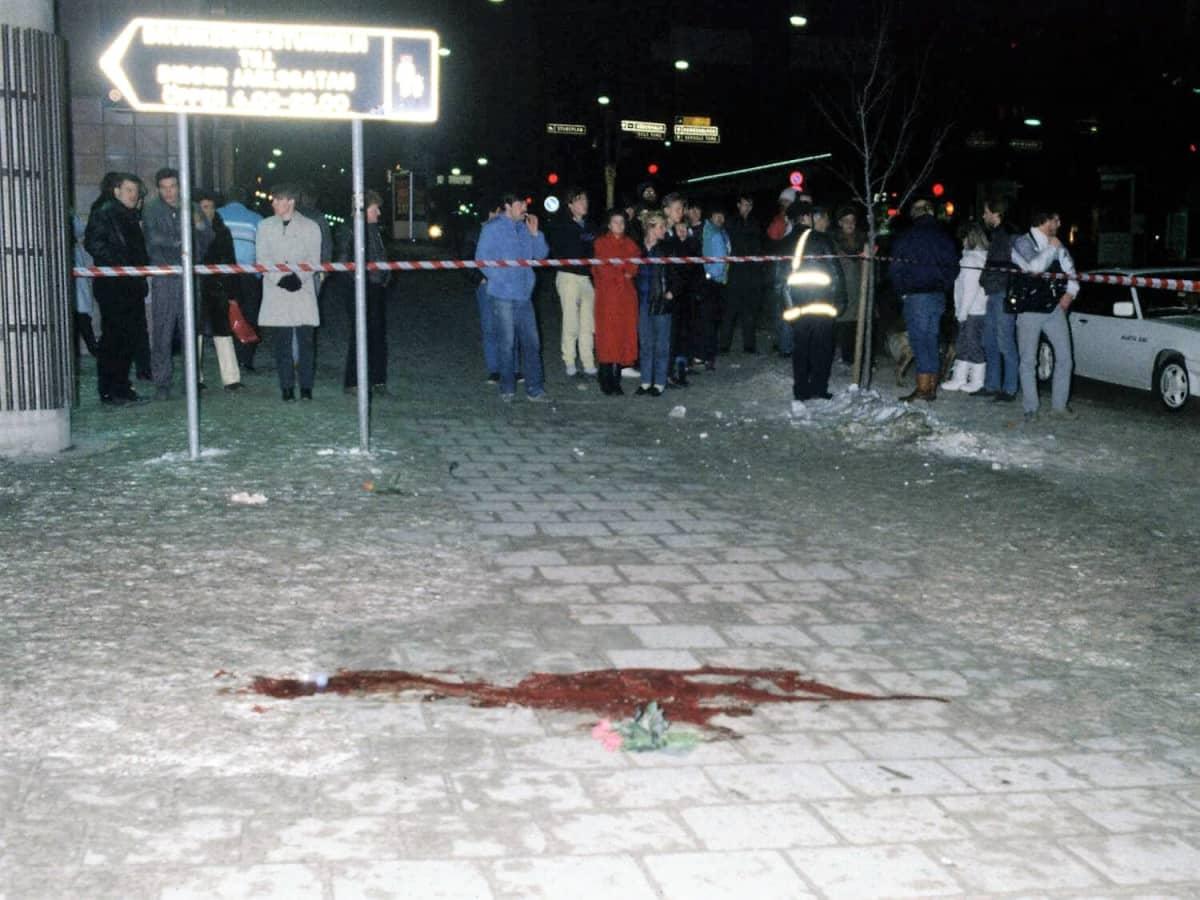 Kadulla on veriläikkä. Paikka on eristetty poliisin nauhalla. Eristyksen ulkopuolella seisoo ihmisiä.