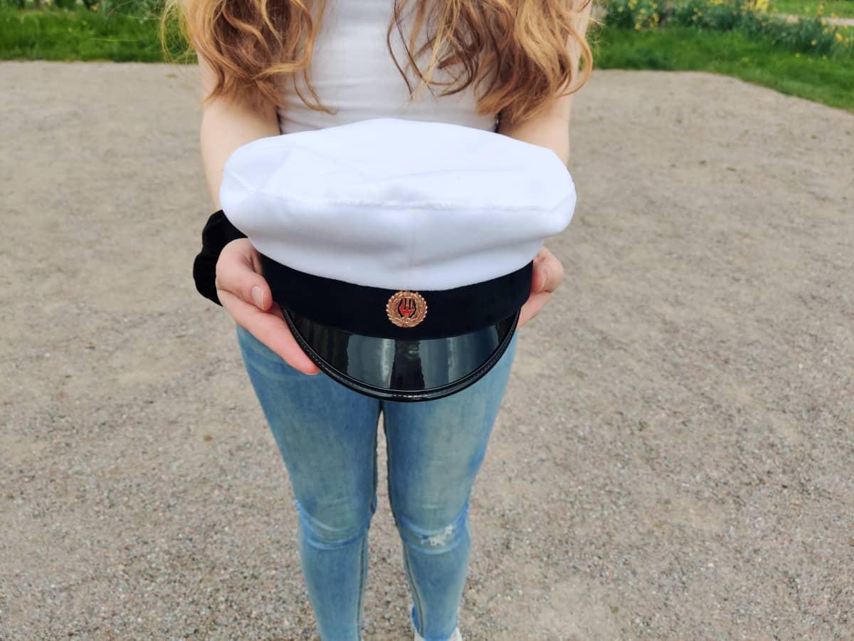 En kvinna håller i en studentmössa i sina händer.