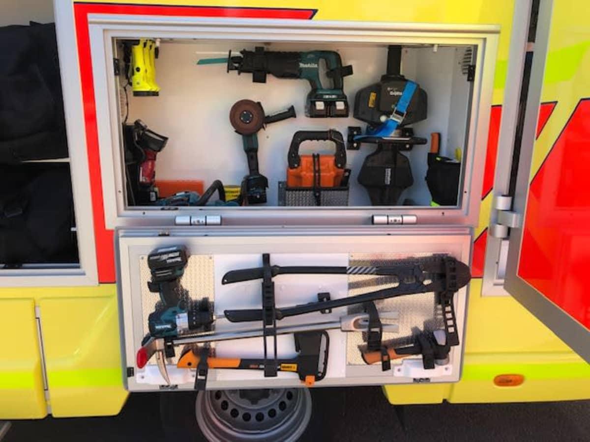 Uuden pelastusauton sivuluukuissa olevia raivaustyökaluja kuten kirveitä, sahoja ja porakoneita
