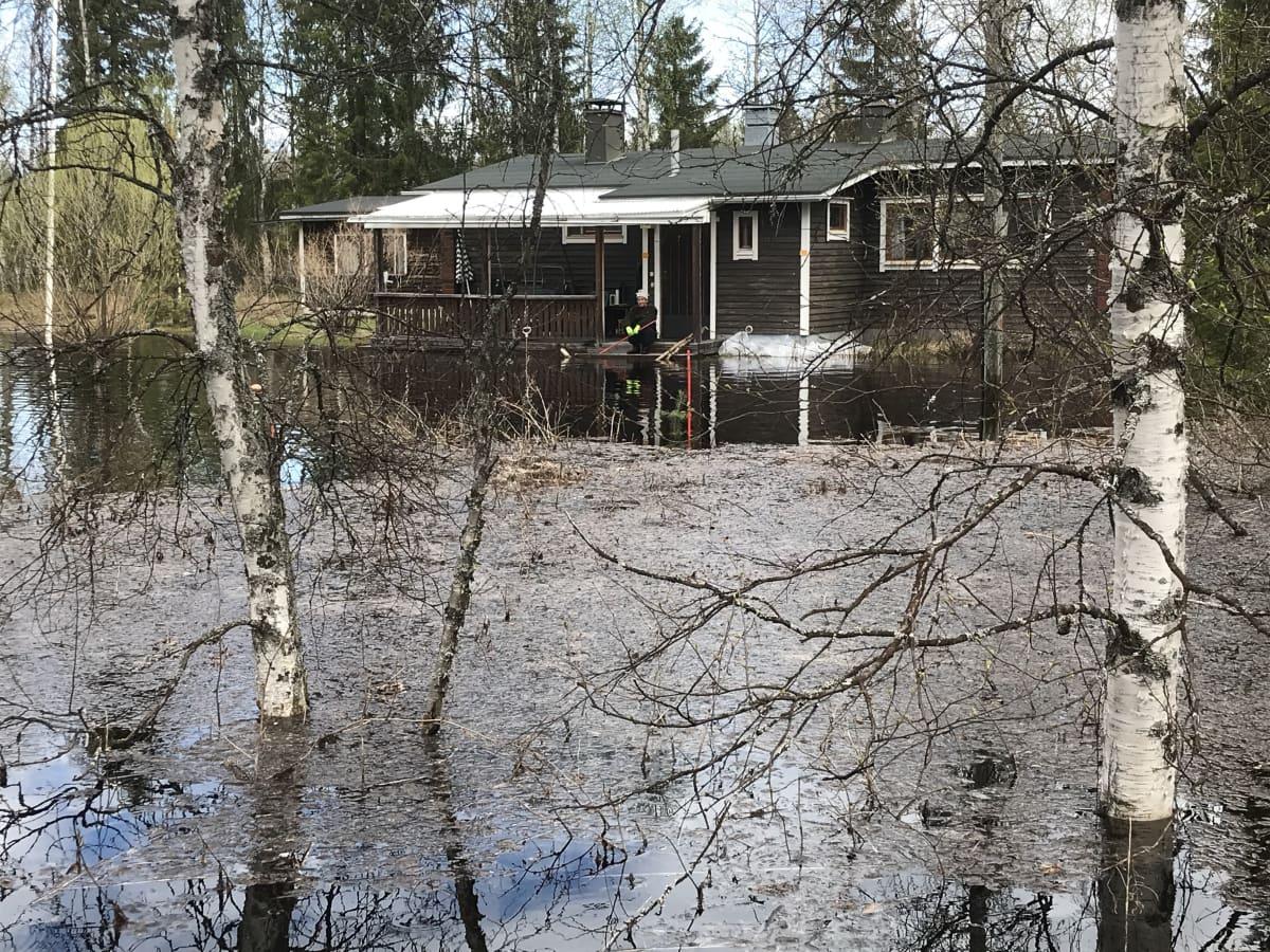Markku Lemmetty tulvaveden ympäröimän mökkinsä portailla