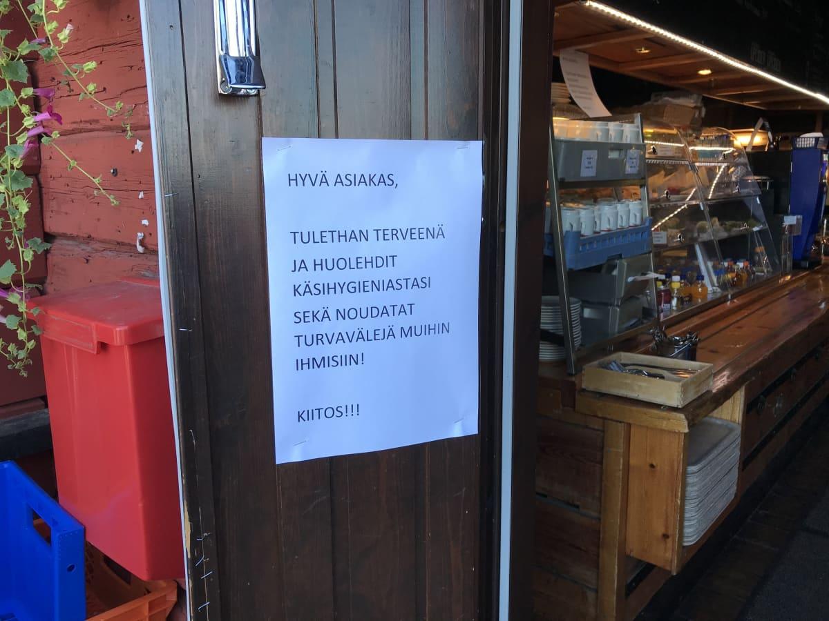 Koronamuistutus Kauppatori Kahvilamakasiiinin ovella Oulussa..