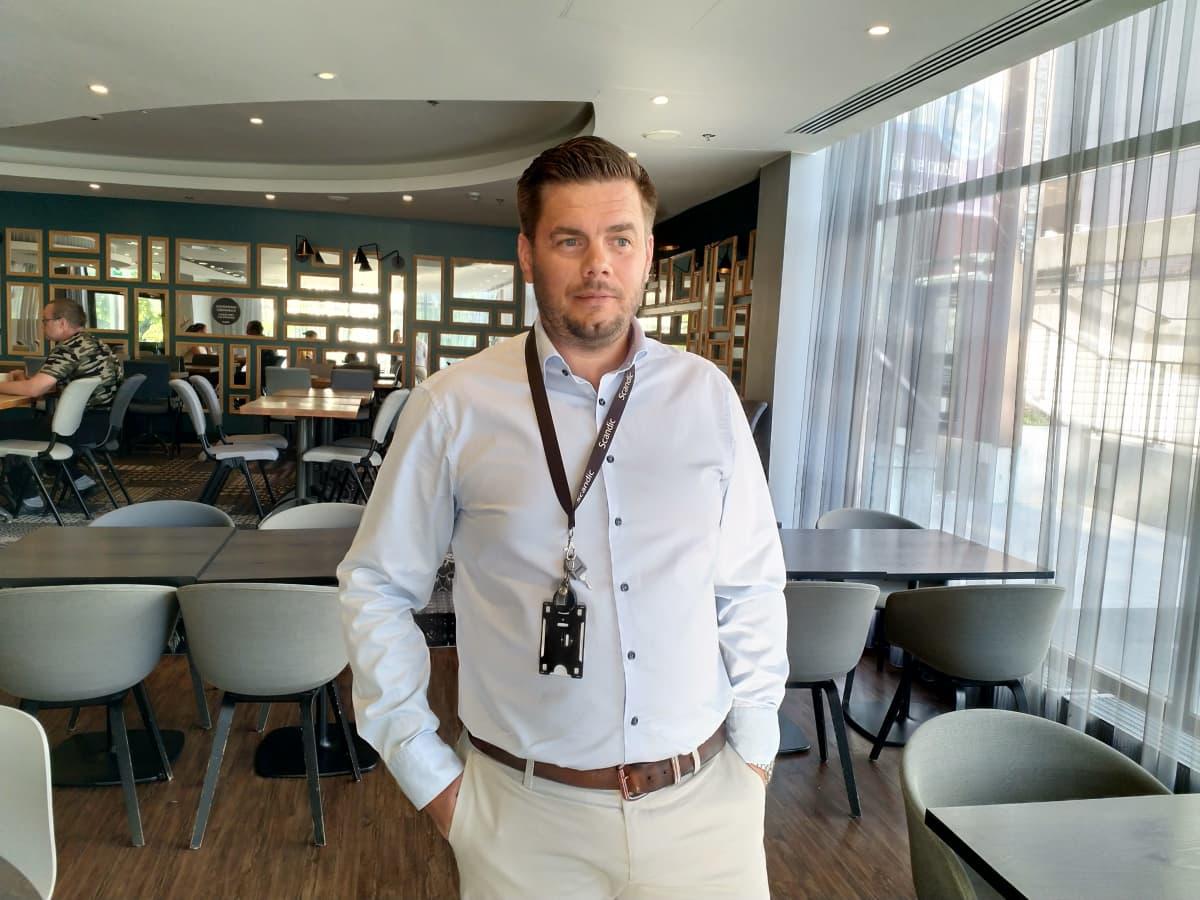 En man i ljusblå kragskjorta och kortklippt hår står med händerna i fickorna och tittar förbi kameran. Han står i en hotellrestaurang.