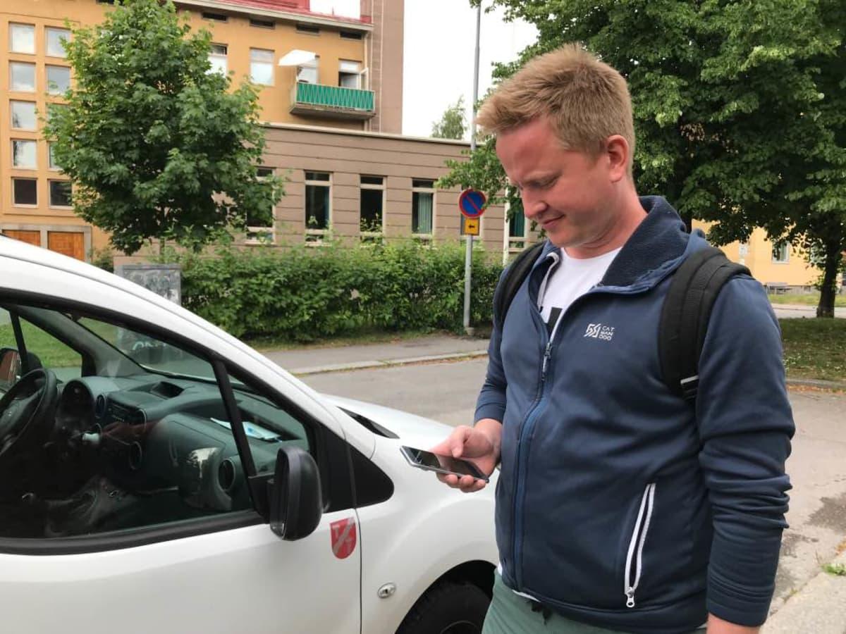 lähihoitaja Hannu Saari tuijottaa kännykän parkkisovellusta