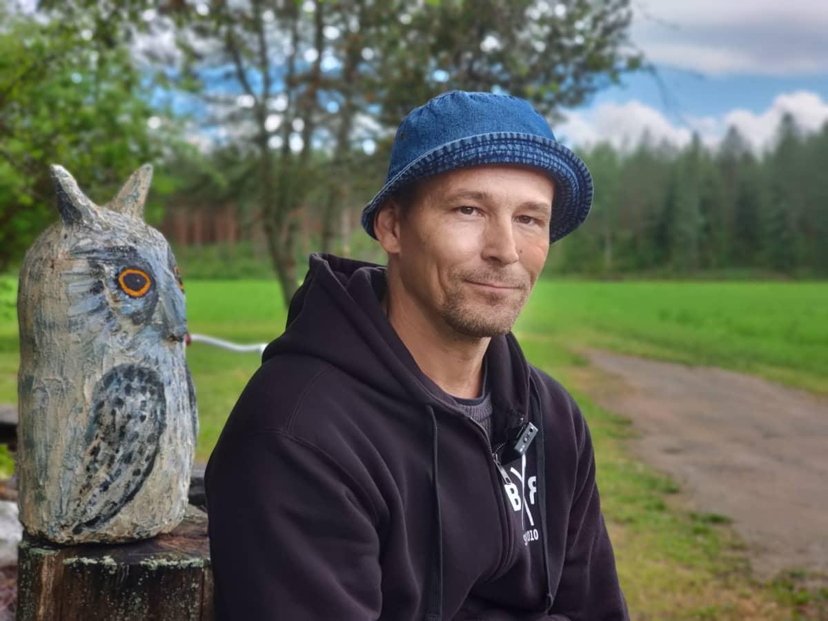 Maanviljelijä Juha Rautiainen istuu kotipihansa portilla