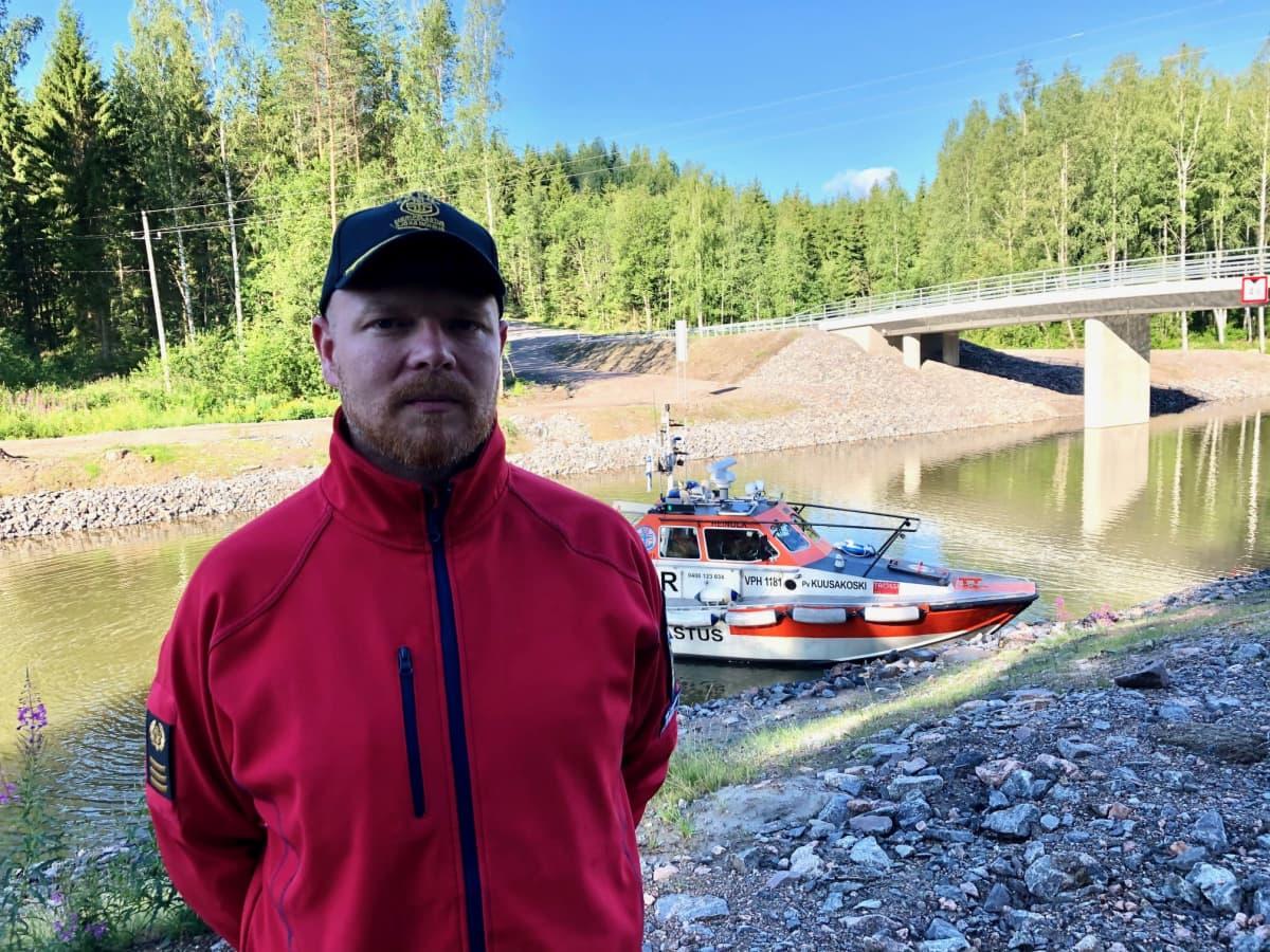Heinolan järvipelastajien puheenjohtaja Sami Salomaa seisoo Kimolan kanavan varrella takanaan yhdistyksen Kuusakoski -pelastusvene.