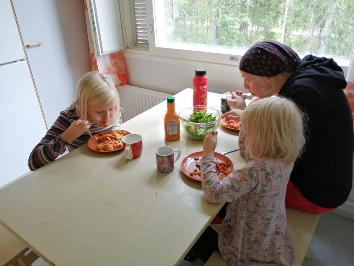 Holapan perhe syömässä vegaanilasagnea pöydän ääressä.