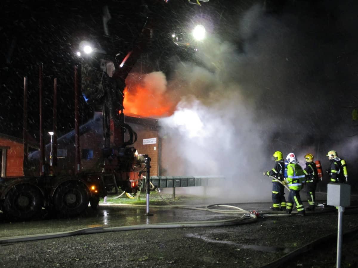 Pelastuslaitos sammuttaa rivitalon tulipaloa.
