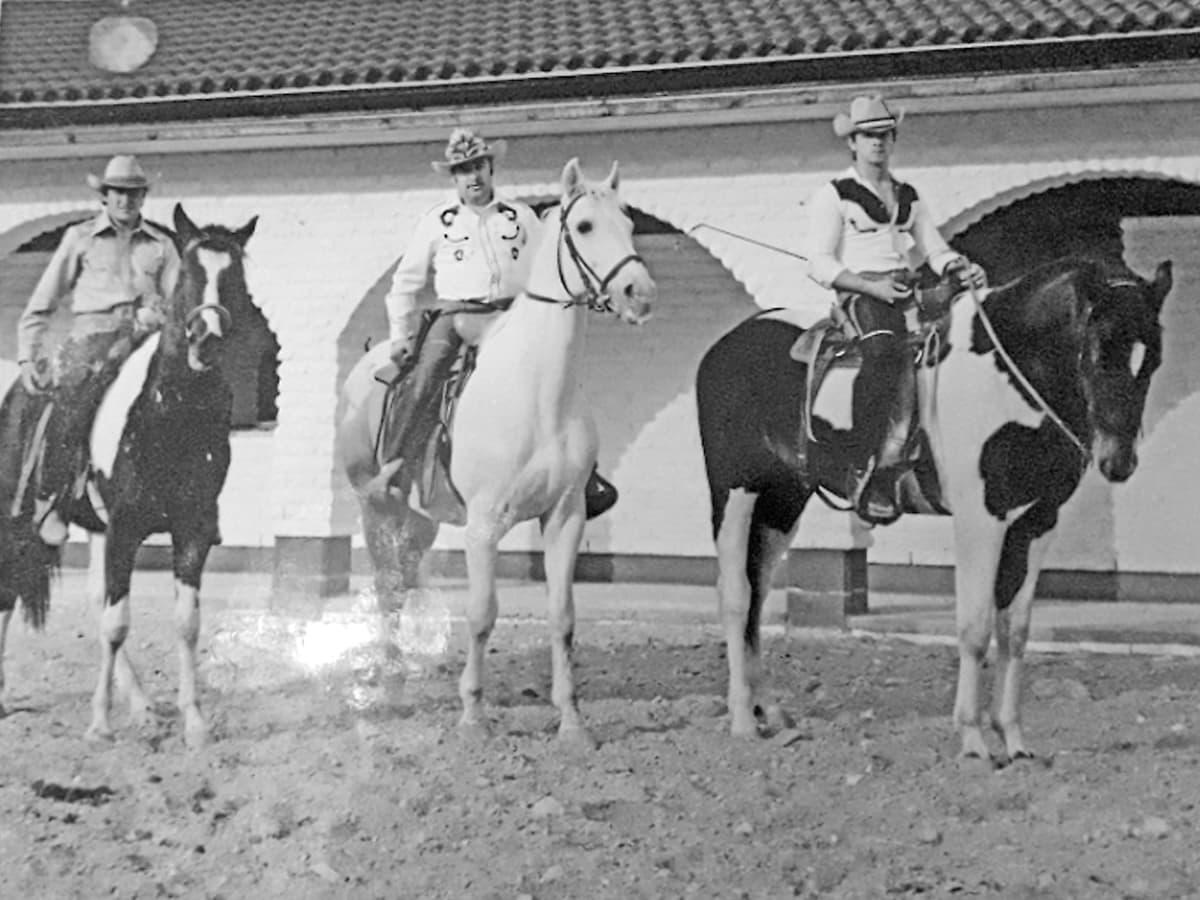 Kolme länkkäriksi pukeutunutt miestä hevosten selässä