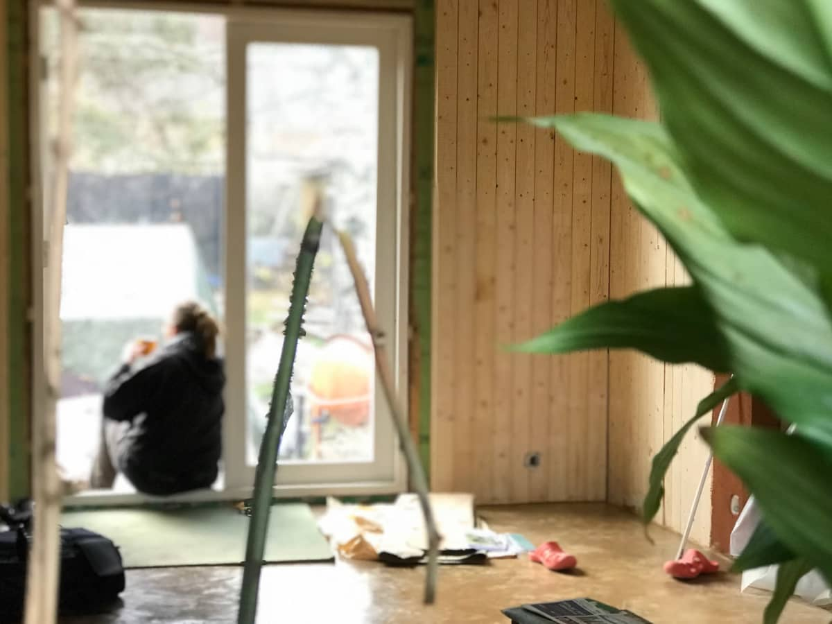 Taustalla nainen istuu selin kuistin oviaukossa, etualalla viherkasvi