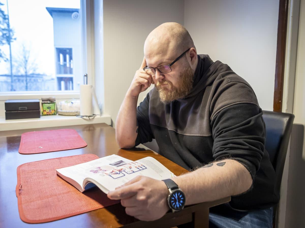 Janne Ostonen lukee oppikirjaa keittiön pöydän ääressä.