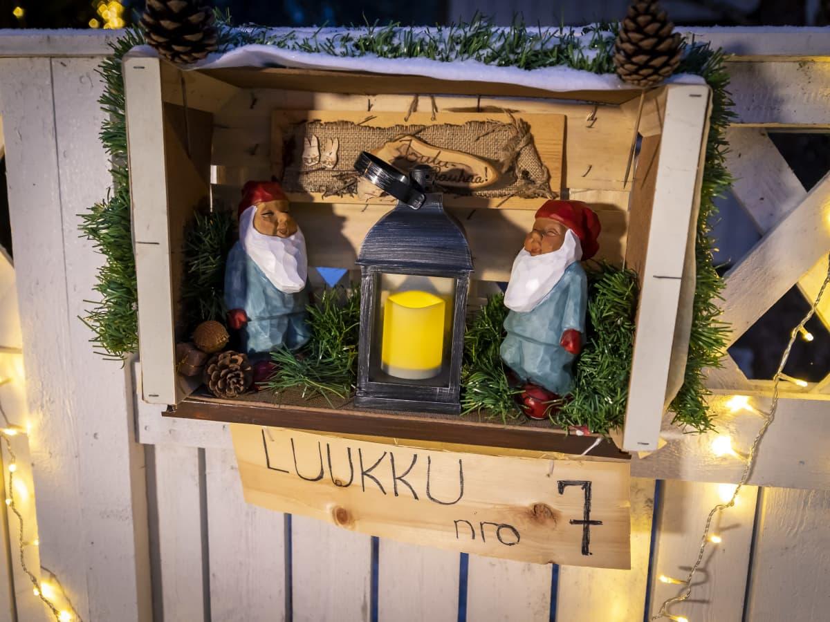 Joulukalenterin luukku 7, jossa on kaksi puista tonttua ja lyhty.