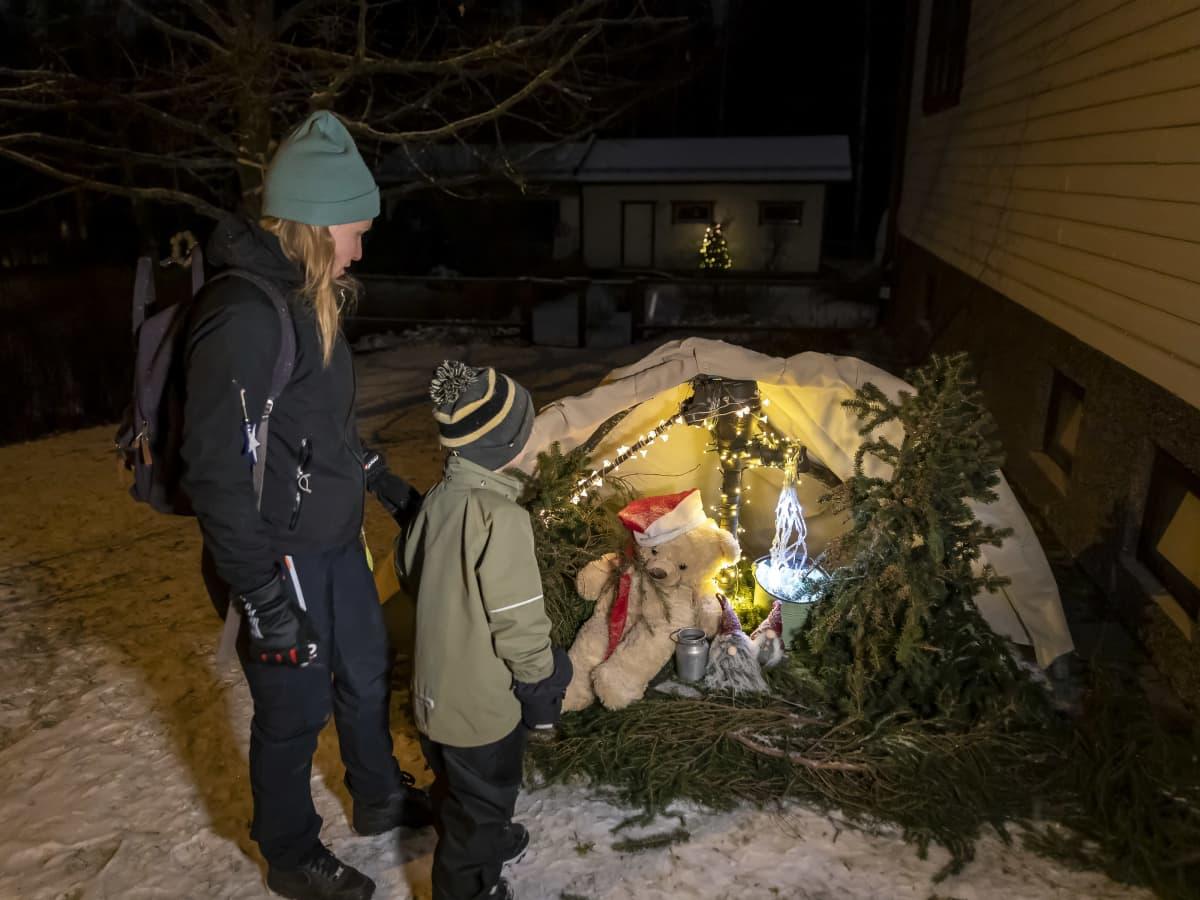 Nainen ja poika katsovat talon pihassa olevaa joulukalentrin luukkua 14, jossa on nalle kaivolla.