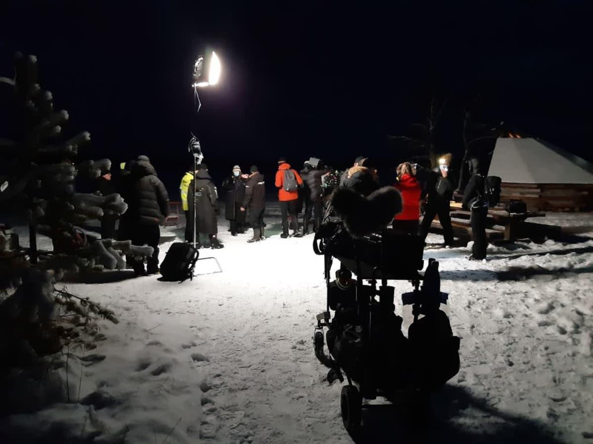Kuvausryhmän jäseniä ja kuvauskalustoa pimeässä talvisessa metsässä