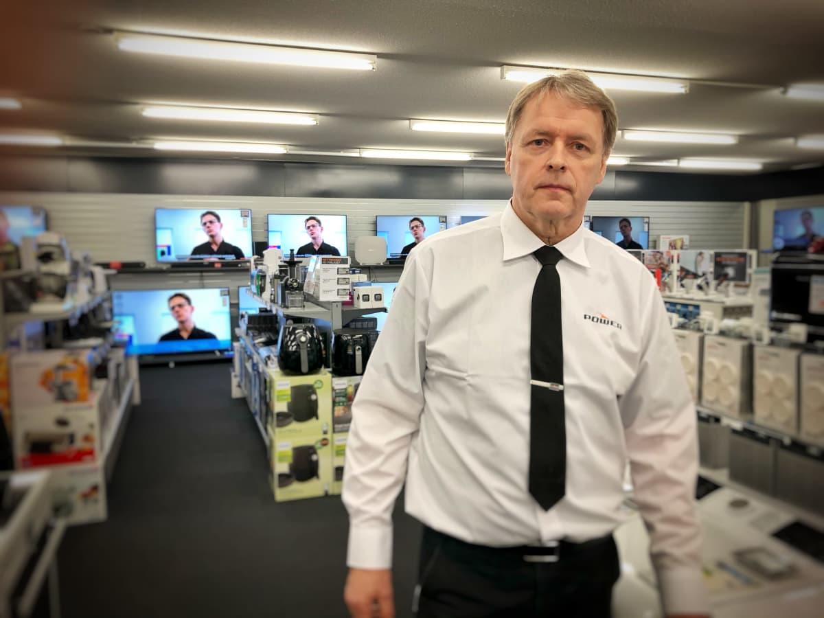 Valkoiseen paitaan pukeutunut kauppias seisoo kodinkoneliikkeessä. Taustalla näkyy televisiota.