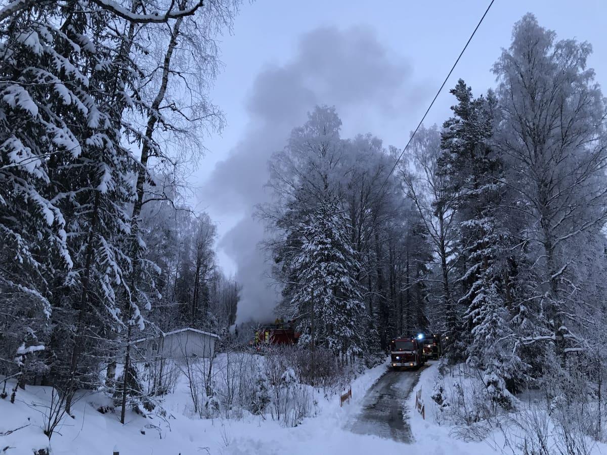 Palanut omakotitalo savuaa talvisen metsän keskellä. Ohi kulkevlla tiellä ja talon luona on paloautoja.
