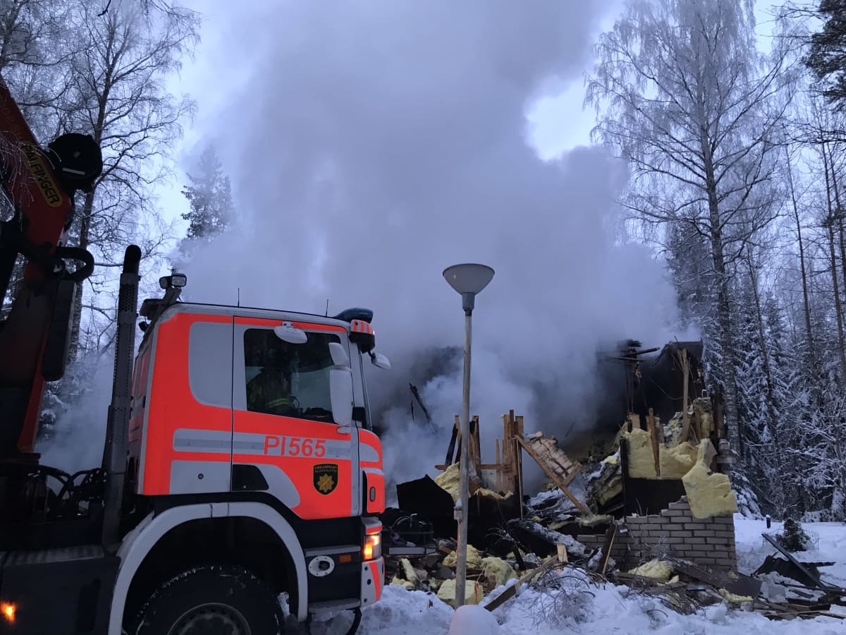 Paloauto tulipalossa tuhoutuneen talon edustalla. Raunioista nousee savuta.