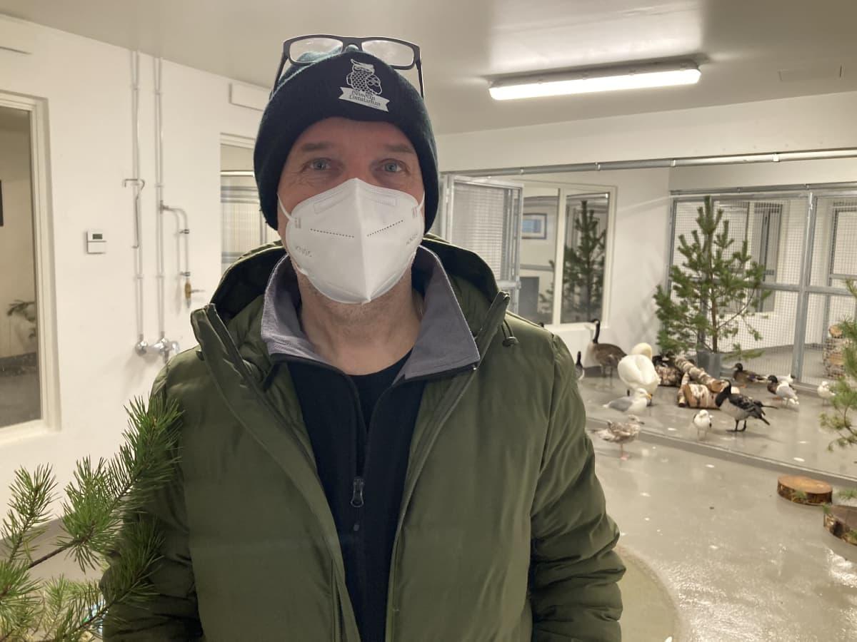 Mies katsoo kameraan maski naamalla, taustalla on joutse ja muita vesilintuja hoitolan sisähäkissä.