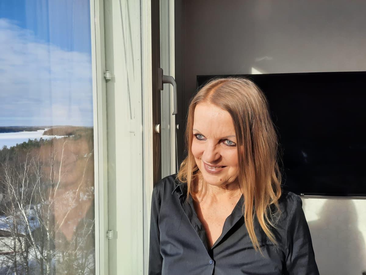 Kirjailija Annamari Marttinen katsoo ikkunasta ulos