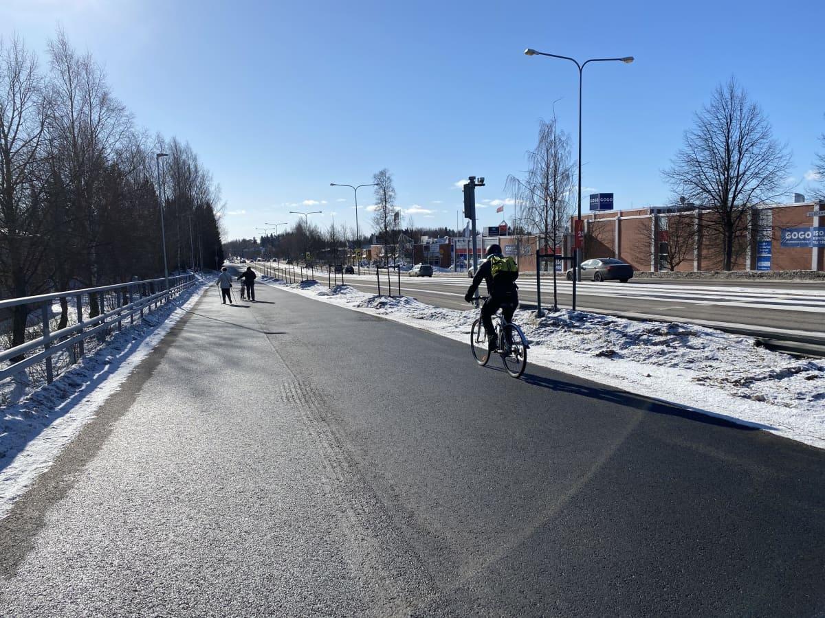 Lahden sula älypyörätie maaliskuussa. Kuvassa pyörilijä, sauvakävelijä ja pyörää ylämäkeen taluttava mies.