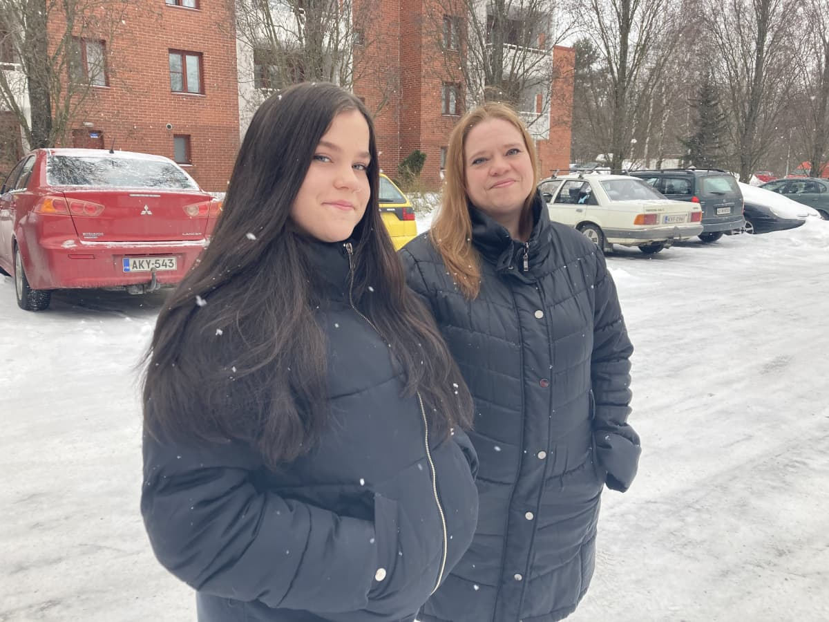 äiti ja tytär seisovat vierekkäin ja katsovat kameraan