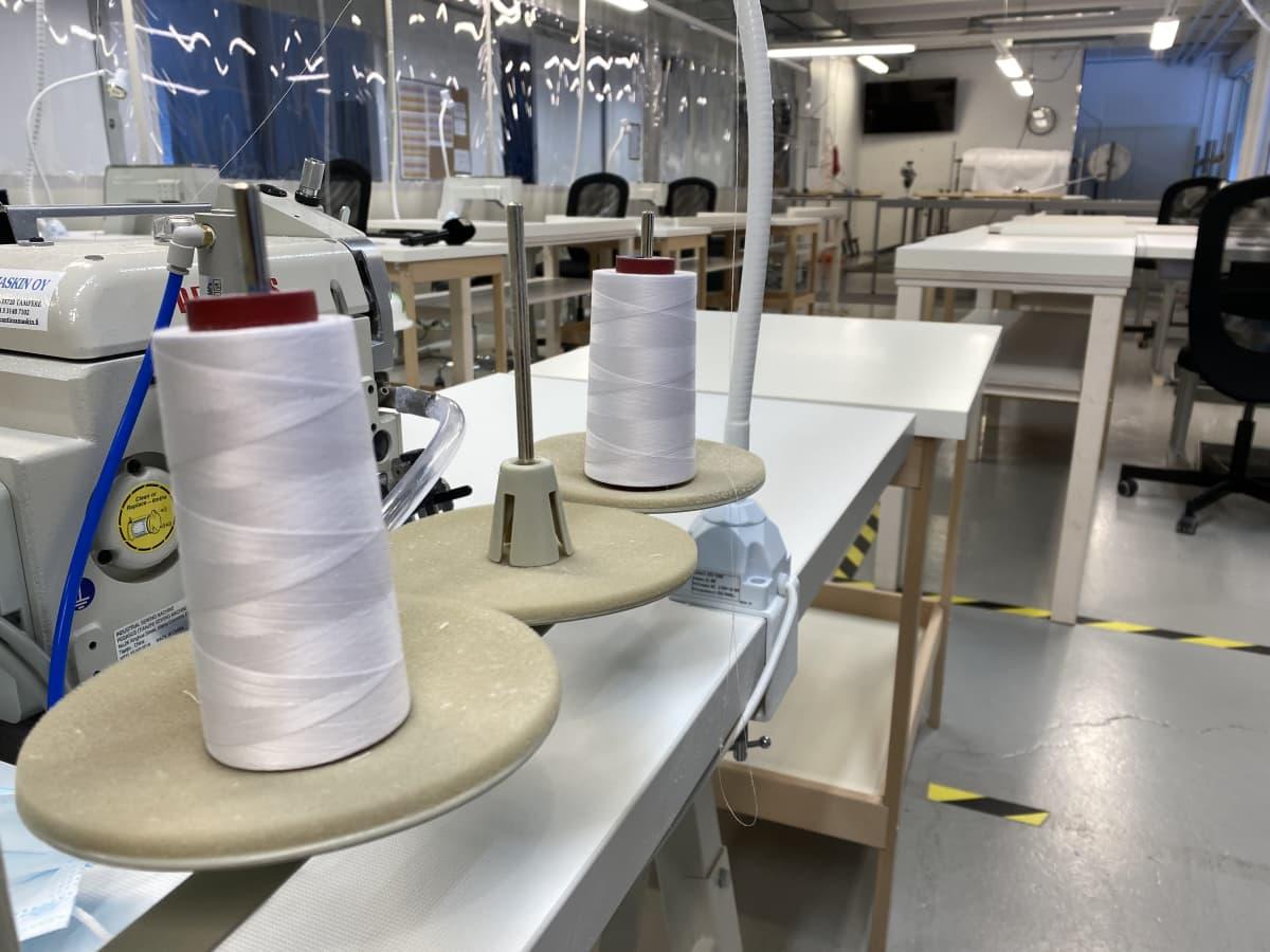 Teollisuushallissa pöydillä on ompelukoneita, lankaa ja kangasta suojavarusteiden ompelemista varten.