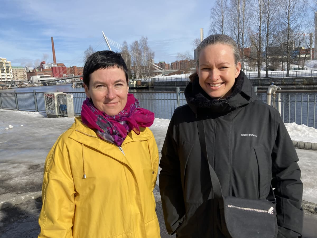 Kaksi naista seisoo keväisessä kaupunkimaisemassa