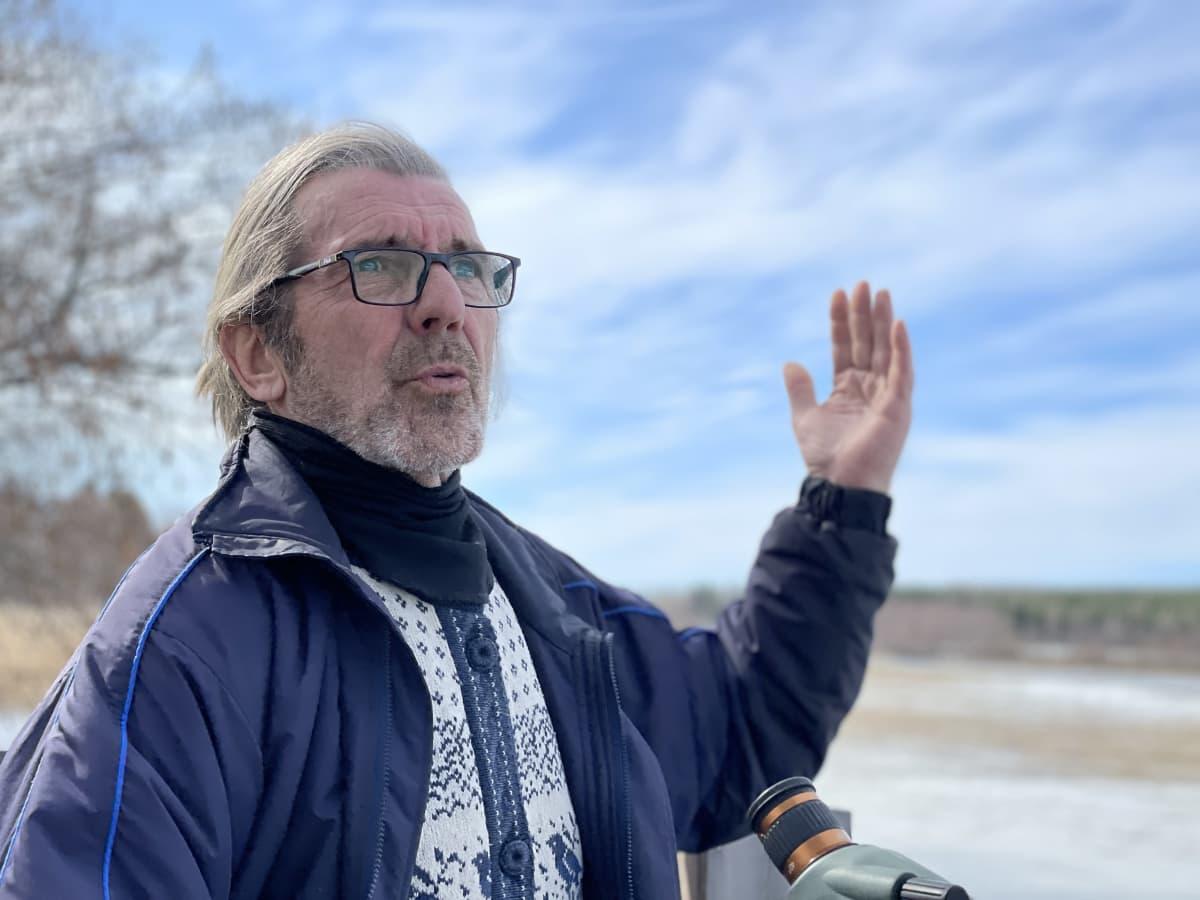 Tapio Osala istuu laiturilla taustalla näkyy keväinen sinivalkoinen taivas