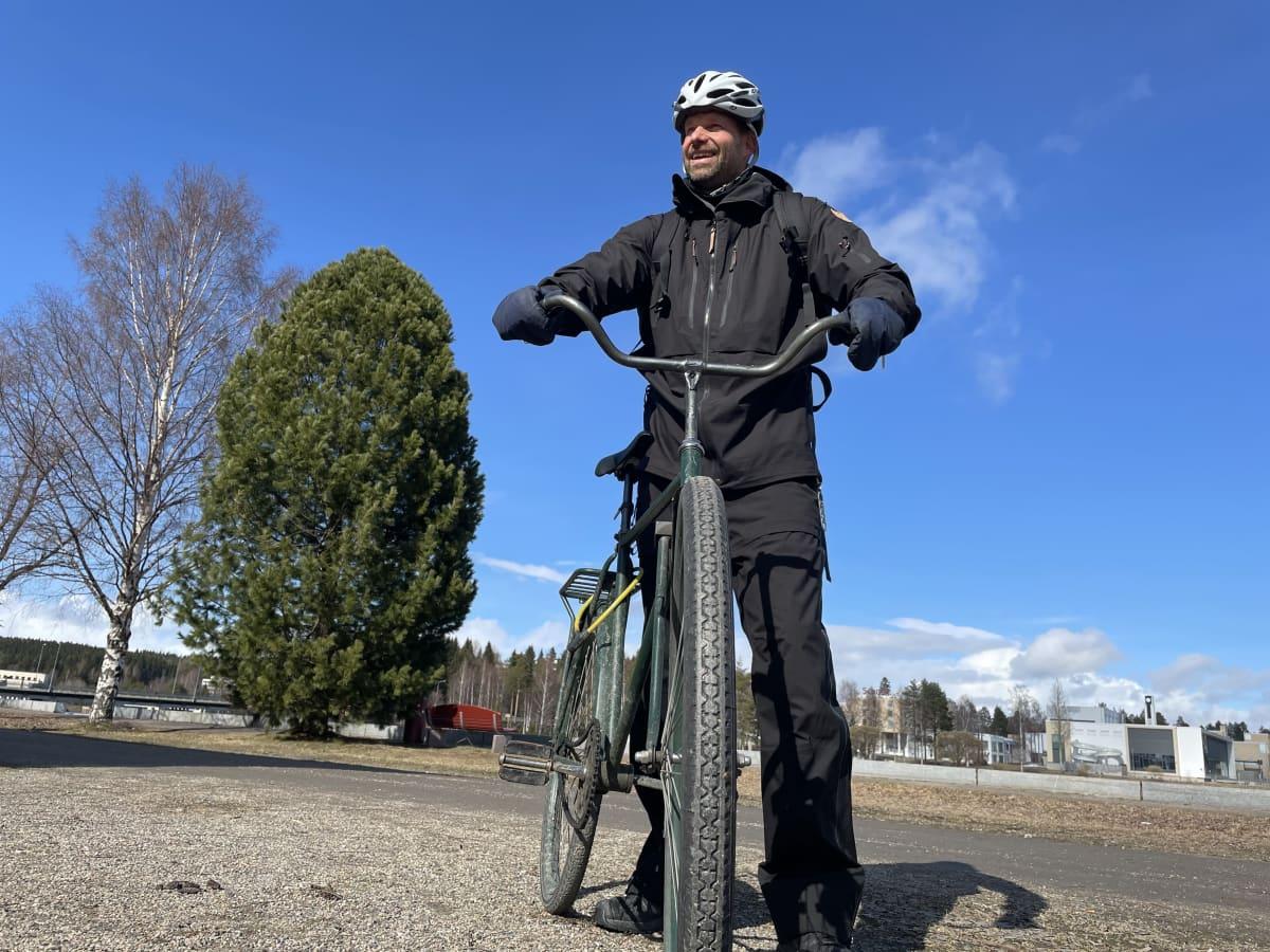 Mies seisoo polkupyörän kanssa