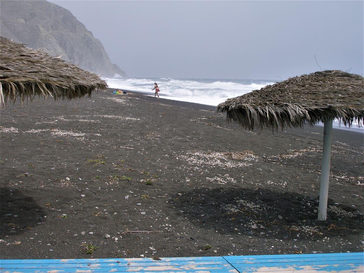Rannalla näkyy aurinkovarjoja ja nainen rantaviivalla