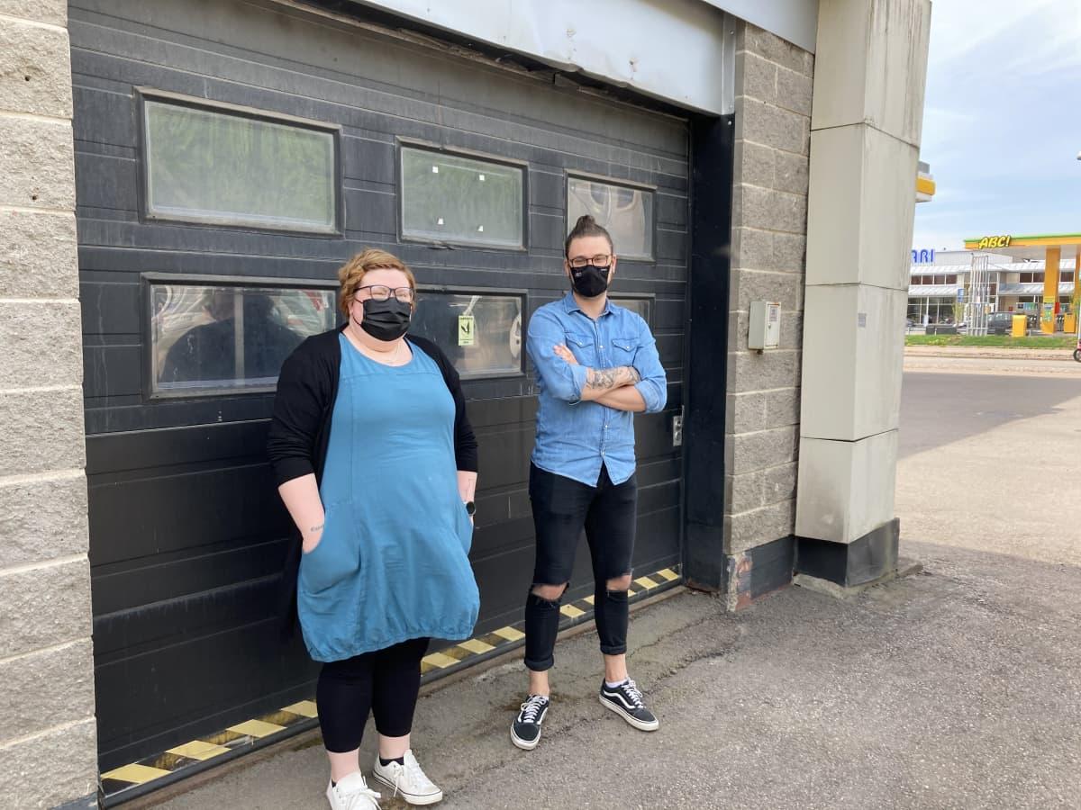 Nainen ja mies seisovat autotallin oven edessä kasvomaskit kasvoillaan.