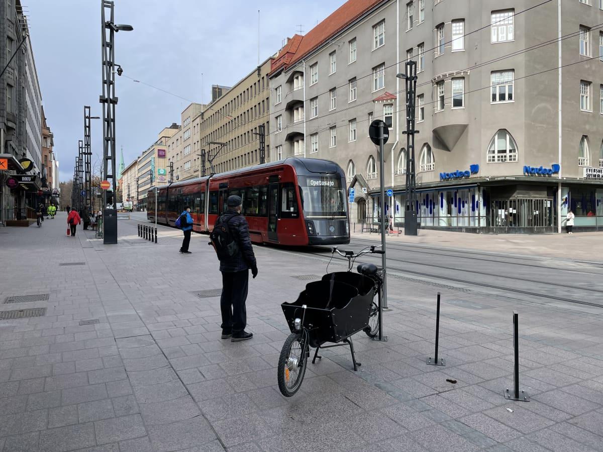 Raitiovaunu ajaa Hämeenkatua itään Kuninkaankadun kohdalla, etualalla taakkapyörä.