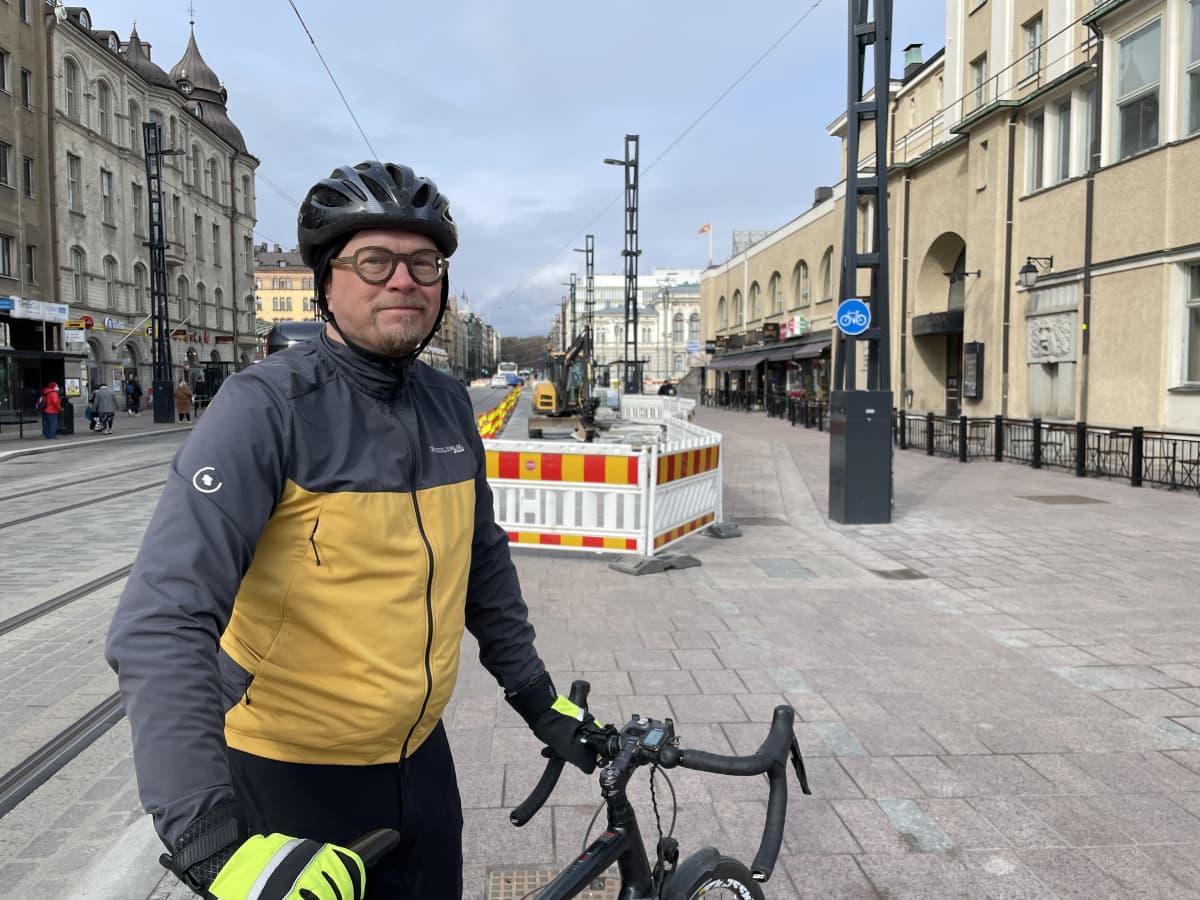 Heikki Kerppilä nojaa pyöräänsä Hämeenkadulla, taustalla näkyy Tampereen Teatteria, raatihuonetta ja Sumeliuksen taloa.